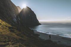 Posi??o do alpinista do homem na rocha da montanha m?xima no por do sol Montanha de Ryten, Noruega fotografia de stock royalty free