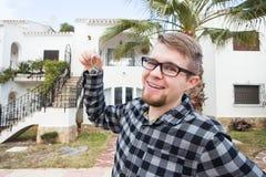 Posiadania, nieruchomości, własności i dzierźawcy pojęcie, - portret rozochocony młodego człowieka mienia klucz od nowego domu zdjęcia stock