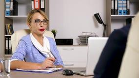 Posibilidad de empleo de la carrera para el hombre de negocios que está dando una entrevista de trabajo a la señora de la hora en almacen de metraje de vídeo