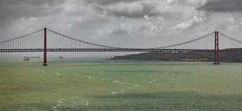 Posibilidad muy remota de 25 de Abril Bridge en Lisboa Fotos de archivo libres de regalías