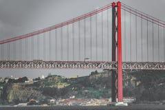 Posibilidad muy remota de 25 de Abril Bridge en Lisboa Imagen de archivo libre de regalías