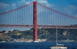 Posibilidad muy remota de 25 de Abril Bridge en Lisboa con el barco de navegación Imagen de archivo