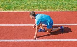 Posición de comienzo baja del soporte del atleta del hombre en la trayectoria del estadio Principio del nuevo hábito de la forma  foto de archivo libre de regalías