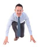 Posición de trabajo asiática del hombre de negocios lista para correr Foto de archivo libre de regalías