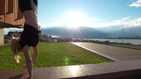 Posición del pino que camina atractiva de la mujer joven en el encintado en la puesta del sol del verano metrajes