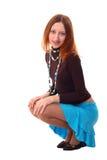 Posición en cuclillas de la muchacha Imagen de archivo