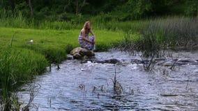 Posición en cuclillas de la mujer en la piedra, río fluído corrido del barco en parque almacen de metraje de vídeo