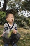 Posición en cuclillas del muchacho en césped Fotos de archivo
