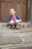 Posición en cuclillas feliz del muchacho Imagen de archivo libre de regalías