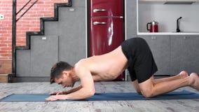 Posición practicante masculina de la cobra de la yogui flexible respecto a vista lateral de la cocina de la estera en casa almacen de metraje de vídeo