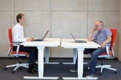 Posición sentada correcta y mala en el escritorio Foto de archivo