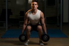 Posiciones en cuclillas con pesas de gimnasia Fotos de archivo