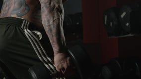 Posiciones en cuclillas con pesas de gimnasia El hombre se pone en cuclillas con pesas de gimnasia en gimnasio Hombre muy fuerte  Fotos de archivo