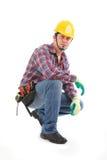 Posiciones en cuclillas de un trabajador de construcción abajo y serio imagenes de archivo