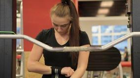 Posiciones en cuclillas en el gimnasio Paurlifting elevación Posiciones en cuclillas con un peso Los trenes de la mujer en el gim almacen de video