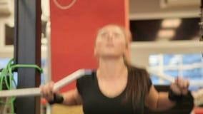 Posiciones en cuclillas en el gimnasio Paurlifting elevación Posiciones en cuclillas con un peso Los trenes de la mujer en el gim almacen de metraje de vídeo