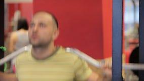 Posiciones en cuclillas en el gimnasio Paurlifting elevación Posiciones en cuclillas con un peso Los trenes del hombre en el gimn almacen de metraje de vídeo