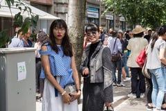Posig de duas mulheres elegantes durante a semana de moda de Milan Men Fotografia de Stock Royalty Free