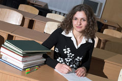 Posing. Attractive student is looking in camera and writing Royalty Free Stock Image