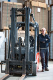 Posing alongside a forklift Royalty Free Stock Photo