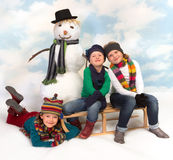 Posing around the snowman. Three little girls on a sledge posing with their snowman Stock Image