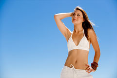 Posing on the beach. A beautiful young girl posing on a blue sky Royalty Free Stock Photos