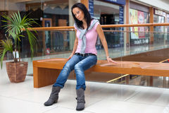 Posing brunette on bench over mall background. Portrait of a posing brunette on a bench over mall background Stock Image