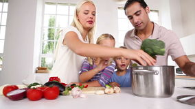 Posing family putting vegetables in a pot Stock Images