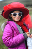 Posing in Fancy Dress Up. Cute little girl playing dress up with a big red fancy hat and sunglasses. Shallow depth of field Royalty Free Stock Photos