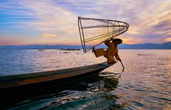 Posing fisherman, Inle Lake, Myanmar. INTHA, MYANMAR - FEBRUARY 18, 2018: The Inle Lake traditional fisherman poses, showing the trick with conical net on the Stock Photography