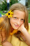 Posing flower. Young girl posing with flower in her hair and chin in hand Stock Photos