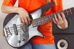Posing hands of artist playing the bass guitar Stock Photos