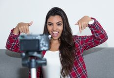 Posing latin american influencer girl recording video blog. With camera at home stock photos
