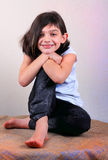 Posing Little Girl. A portrait of an unprofessional smiling innocent, little preteen girl sitting posing on burlap. Shallow depth of field Royalty Free Stock Images