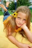 Posing lying. Young girl on blanket posing with flower in her hair Royalty Free Stock Image
