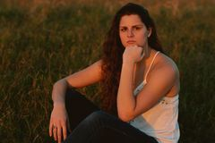 Posing modelo femenino moreno cabelludo rizado largo atractivo y sonrisa para la cámara afuera Fotografía de archivo