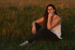 Posing modelo femenino moreno cabelludo rizado largo atractivo y sonrisa para la cámara afuera Imagenes de archivo