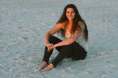 Posing modelo femenino moreno cabelludo rizado largo atractivo y sonrisa para la cámara afuera Fotos de archivo