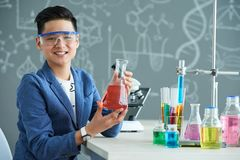 Posing for Photography at Chemistry Classroom. Joyful Asian boy wearing protective goggles posing for photography with wide smile while holding flask in hands Stock Image