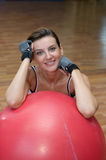 Posing during Pilates with Ball. A beautiful woman posing on a red pilates ball Stock Photos
