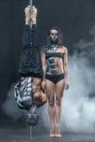 Posing of pole dance couple in dark studio Royalty Free Stock Image