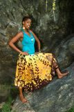 Posing on the rock. African American woman poses on a large rock stock photography