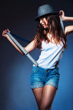 Posing sexy woman in hat and shorts with suspenders Stock Photo