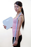 Posing sporty woman with scale and tape measure Royalty Free Stock Photos