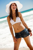 Posing in the sun. An attractive young woman on the beach Royalty Free Stock Images