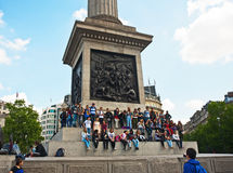 Posing in Trafalgar Square. Large group of young people posing in Trafalgar Square on the base of Nelson's Column Stock Photos