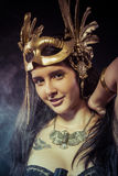 Posing warrior woman with gold mask, long hair brunette. Long ha Stock Images