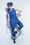 Posing woman in denim hat and jumpsuit Stock Image