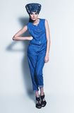 Posing woman in denim jumpsuit and hat Royalty Free Stock Photography
