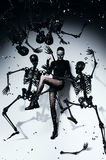 Posing woman in torn pantyhose with skeletons. In studio Royalty Free Stock Image